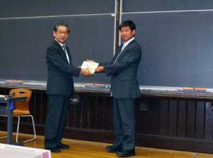 目録を手渡す田口社長(右)