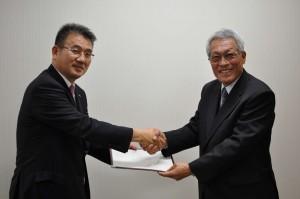 握手するティーエルロジコムの鎌田社長(左)とJVC・ケンウッド・ホールディングスの河原会長(右)